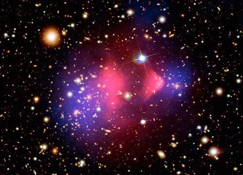 This image of the Bullet cluster shows a separation of dark matter from the luminous matter, with the dark matter shown in blue and the luminous matter shown in red. Image credit: X-ray: NASA/CXC/CfA/M.Markevitch et al.; Optical: NASA/STScI; Magellan/U.Arizona/D.Clowe et al.; Lensing Map: NASA/STScI; ESO WFI; Magellan/U.Arizona/D.Clowe et al.