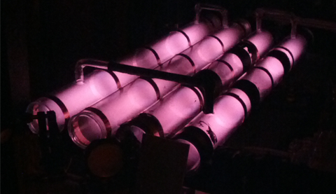 Long tubes of helium glow a soft pink, excited by the radio frequency discharge of the coils wrapped around them.