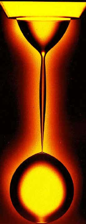 Physicist's lava lamp. Glycerin drips through a viscous oil, showing the details of pinching off in slow motion. Researchers have verified theories of the geometry at the point of snap-off (the narrowest point just above the spherical drop that has formed). Image credit: Phys. Rev. Lett. 83, 1147 (1999)