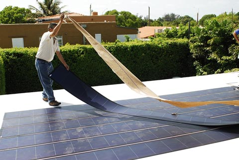 A man lays out thin film solar cells, an older technology for flexible solar panels.